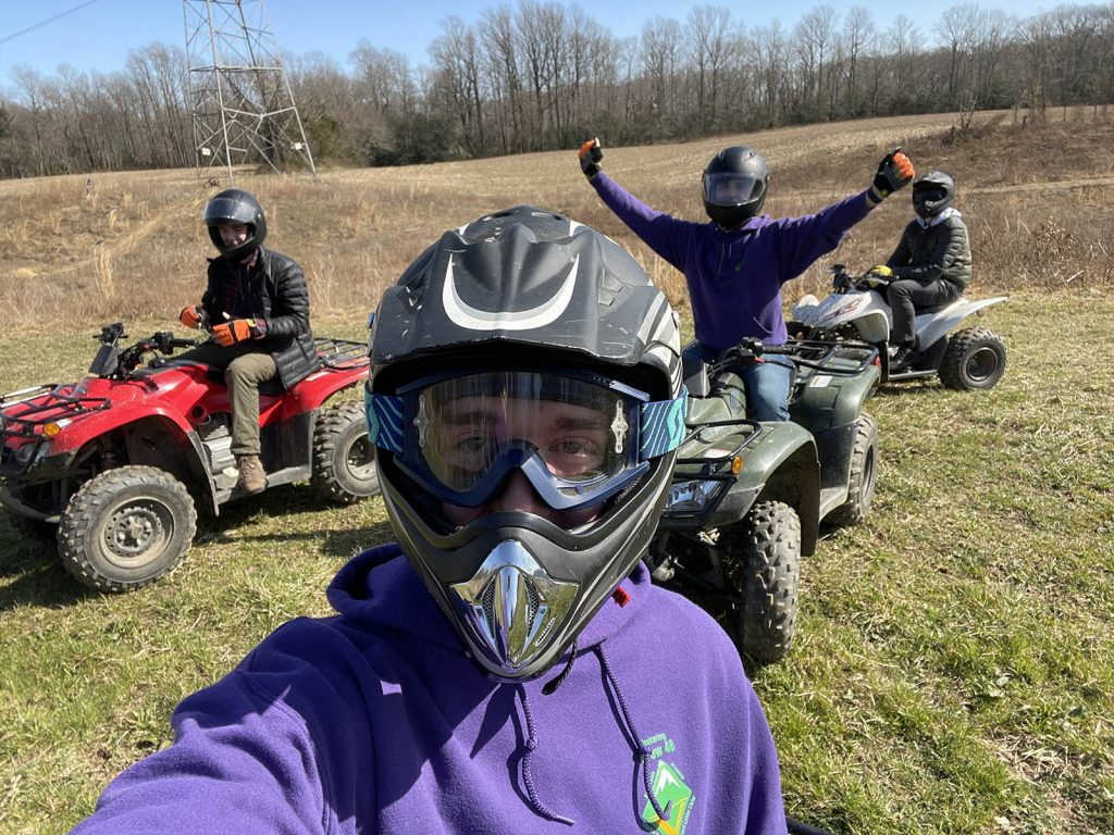 4 members of a Venturing Crew find Adventure by riding all terrain vehicles in an open field