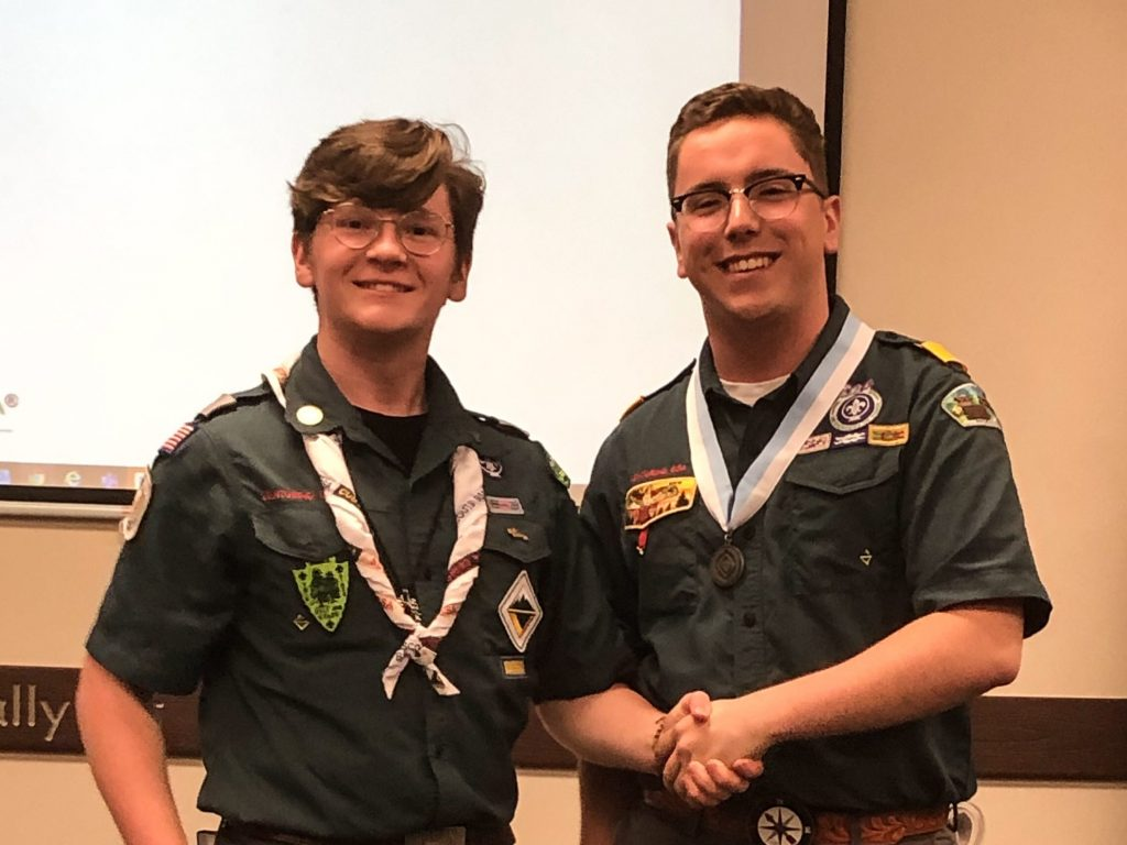 2 Venturers in green field uniforms shake hands at a leadership conference