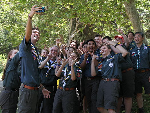 A large group of Venturers in their green field uniforms pose for a group selfie